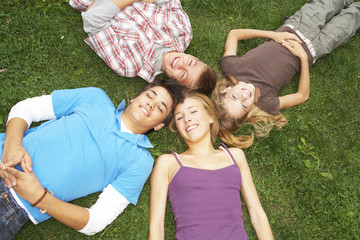 Teenagers lying down on the grass.