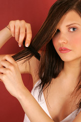 A portrait of a young woman combing her hair.