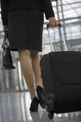 A woman dragging her trolley bag at the airport.