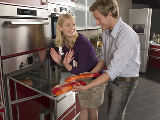Side profile of a young couple taking out a dish from a microwave