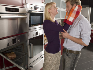 Side profile of a young woman holding a young man's face with oven mitts