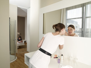 Woman applying make up in the bathroom.