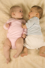 Two babies lying down together.