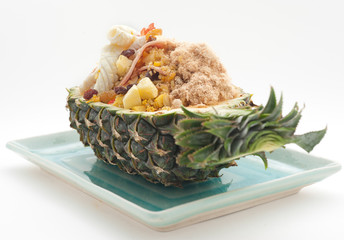 Fried rice with raisings and squid and ham served in pineapple