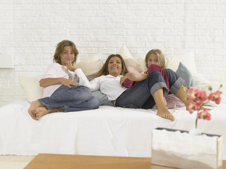 Portrait of a mid adult woman and her children lying down on the bed