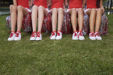 Low section view of five cheerleaders sitting side by side