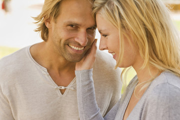 Side profile of a young woman touching a young man's face and smiling