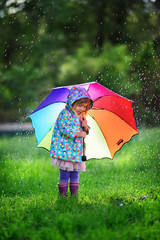 cute toddler girl wearing raincoat with colorful umbrella playin
