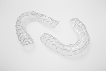 Translucent upper and lower essix retainers on a gray background