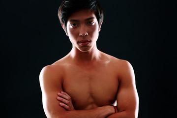 Portrait of a handsome asian man over black background