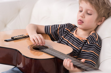 Smiling caucasian boy is playing the acoustic guitar.