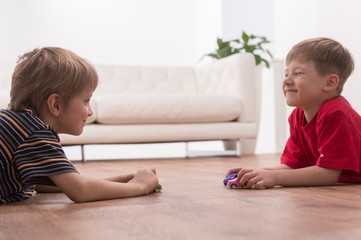 Two friends playing on floor at home.