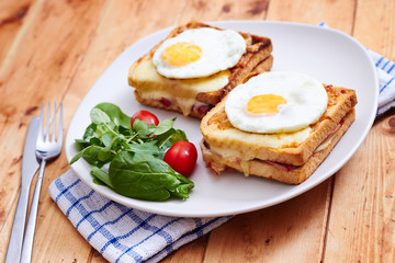 Croque monsieur with eggs and salad on vintage table wide