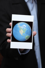 Businessman holding a photo of the Earth in his hand