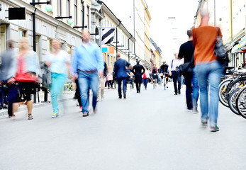 City street with motion blurred pedestrians and bicycles