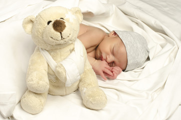 Beautiful innocent newborn sleeping protected by a bear toy
