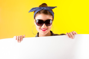 beautiful young retro girl holding white paper over yellow