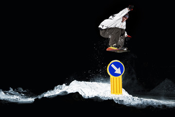 snowboarder jumps over a road sign