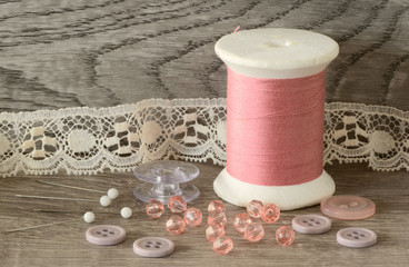 Close up of pink cotton threads spools, bids, and buttons