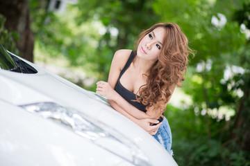 Sexy girl in black vest is posing on hood car