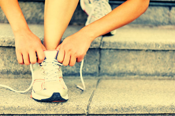 young fitness woman tying shoelaces on stairs