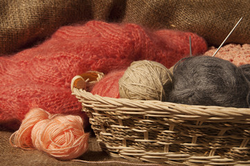 Multicolored yarn balls in a straw basket on the sacking