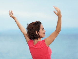 Beautiful young woman enjoying summer with her arms outstretched