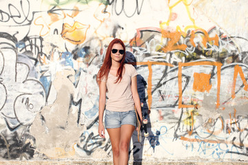 girl with skateboard on background of graffiti