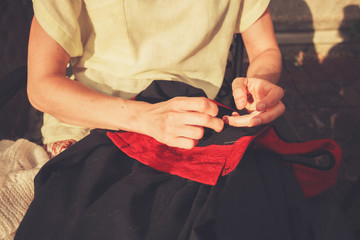 Young woman sewing outside