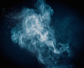 Fototapete - Blue powder exploding isolated on black