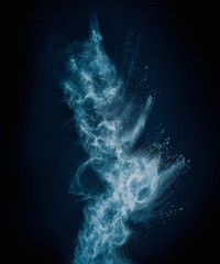 Wall Mural - Blue powder exploding isolated on black