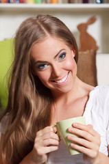 Close-up portrait of a beautiful young woman drinking a cup of t