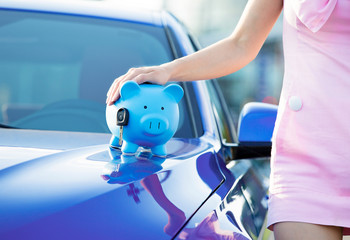 Cropped image woman customer car, piggy bank, key on hood