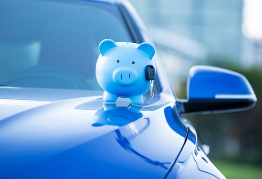 Piggy bank and key on a hood of new car, loan, finance concept