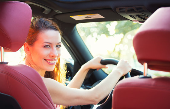 Happy woman driving her new car, turning head to rear passenger