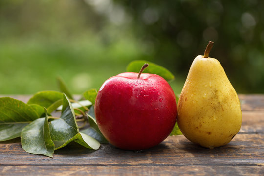 Fresh apple and pear on wooden table