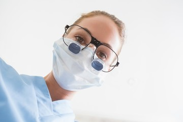 Dentist in surgical mask and dental loupes