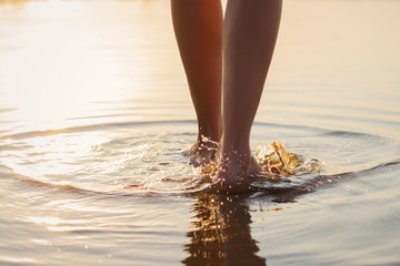 Woman walking in the shallow water at sunset