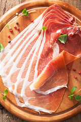 sliced prosciutto ham on chopping board with oregano and pepper