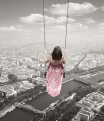 Obraz Young woman on a swing on the Paris town backround. Surrealism c - fototapety do salonu