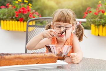 Kleines Mädchen beim Schokoladenkuchen verzieren