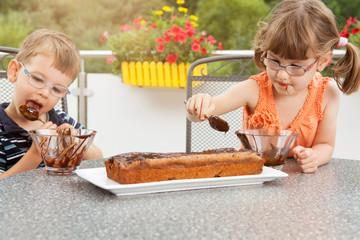 Kinder beim Schokoladenkuchen verzieren