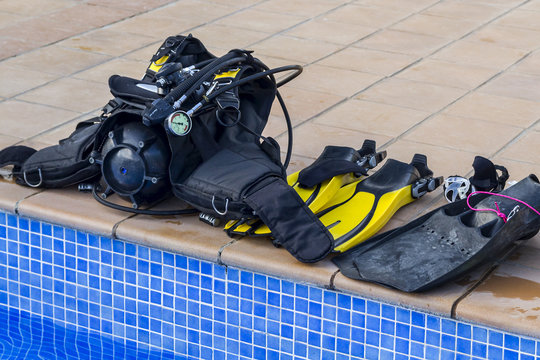 Scuba diving equipment on the edge of a pool