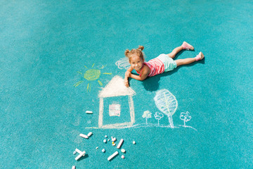 Little girl drawing chalk image on the ground