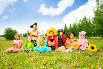 Wall Mural - Happy kids in Halloween costumes sit on grass