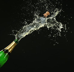 Bottle of champagne with splashes on black background