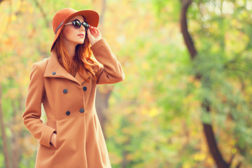 Redhead girl in sunglasses and hat in the autumn park. Wall mural