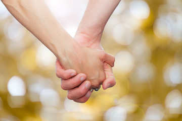 couple holding hands  on glittering background