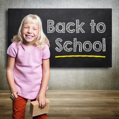 kid standing in front of a blackboard with text 'back to school'