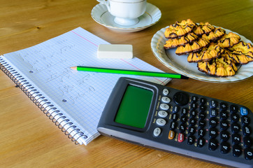workplace, study place with calculator, workbook, cup of coffee
